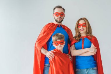 family of superheroes in masks and cloaks looking at camera isolated on grey