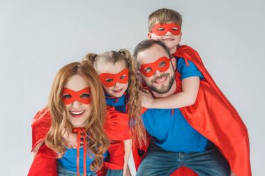 super family in masks and cloaks having fun together and smiling at camera isolated on grey