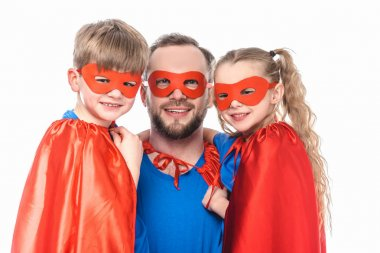 happy father and kids in superhero costumes smiling at camera isolated on white