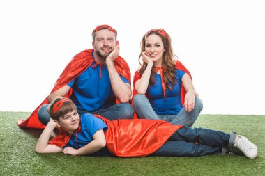 happy family of superheroes sitting on lawn and smiling at camera on white