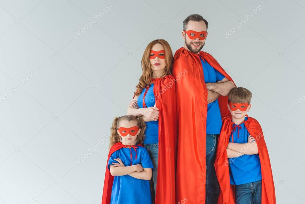 Super family in masks and cloaks standing with crossed arms and looking at camera isolated on grey