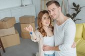 Photo happy young couple smiling at camera while holding key from new apartment