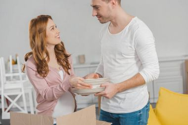 happy pregnant couple holding dishware and smiling each other during relocation