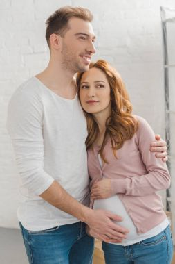 happy pregnant couple embracing and looking away at home
