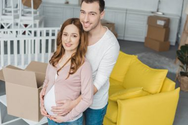 high angle view of happy pregnant couple smiling at camera in new apartment