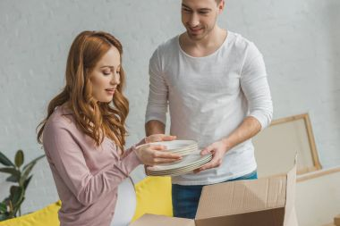 young pregnant couple packing plates in cardboard box during relocation