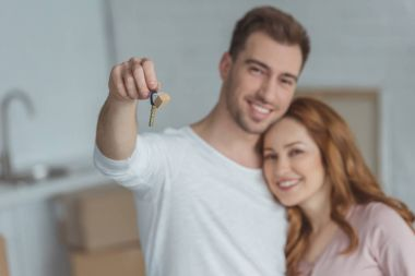 happy young couple holding key from new home and smiling at camera