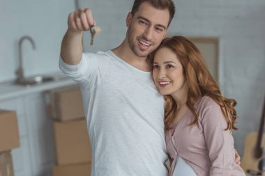 happy young couple looking at key from new apartment