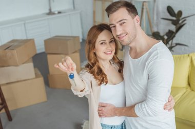 happy young couple smiling at camera while holding key from new apartment
