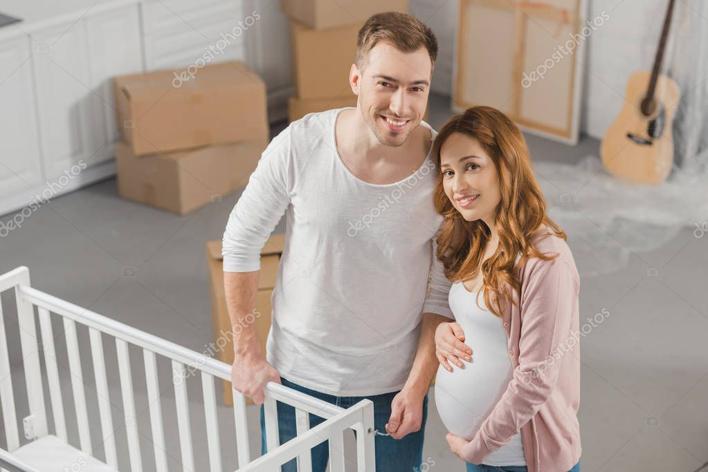 High angle view of happy young pregnant couple smiling at camera while standing near baby bed