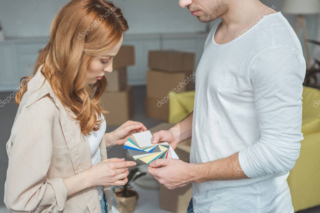 Cropped shot of young couple picking color from palette during renovation and relocation