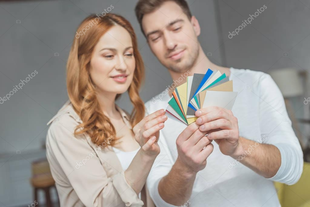 Smiling young couple looking at palette and picking color during renovation apartment