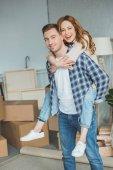 usmívající se pár vezou na nový byt s lepenkových krabic, přemístění koncepce