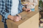 Photo cropped shot of man signing cardboard box with wife with books in hands near by, moving home concept