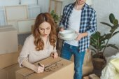 Photo partial view of woman signing cardboard box with husband with dishes near by, moving home concept