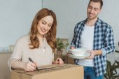 Photo smiling woman signing cardboard box with husband with dishes near by, moving home concept