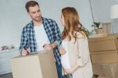Fotografie těhotná žena a muž v novém bytě, přemístění koncepce