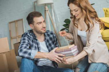 happy young couple packing books while moving home
