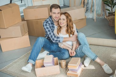 happy young couple sitting together and smiling at camera while packing boxes during relocation