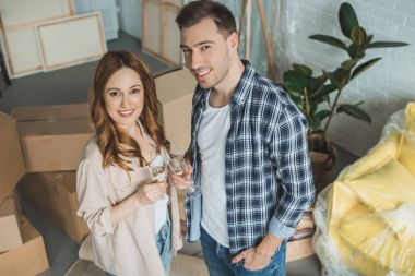 couple holding glasses of champagne and smiling at camera while celebrating relocation