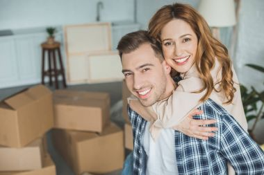 portrait of happy wife hugging husband at new home with cardboard boxes, relocation concept