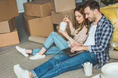 couple eating asian food while using laptop at new apartment, moving home concept