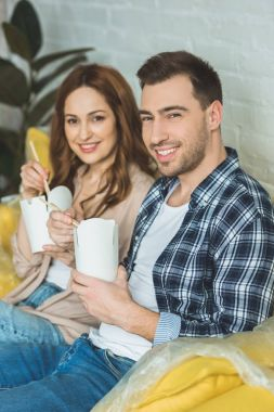 smiling couple eating asian food at new apartment, moving home concept