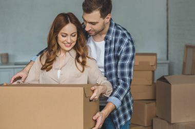 portrait of smiling couple with cardboard box at new home, moving house concept