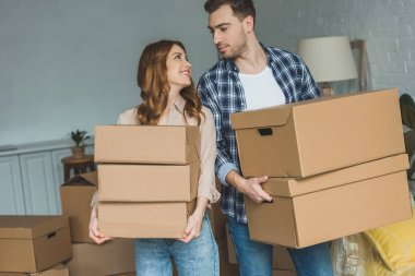 portrait of young couple with cardboard boxes looking at each other at new home, moving house concept