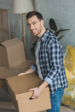 smiling man with cardboard box in hands at new home, relocation concept