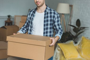 partial view of man with cardboard box in hands at new home, relocation concept