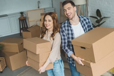 portrait of young couple with cardboard boxes at new home, moving house concept