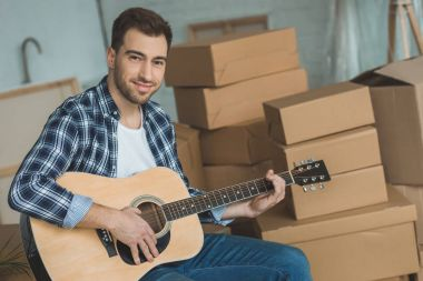 portrait of smiling man with acoustic guitar at new home with cardboard boxes, relocation concept