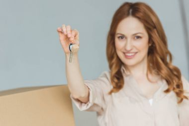 smiling woman showing keys from new apartment in hand, relocation concept