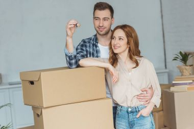 portrait of smiling couple looking at keys from new apartment, relocation concept