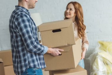 partial view of smiling woman and husband holding cardboard boxes together at new apartment, moving home concept