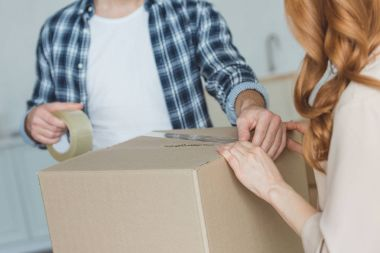cropped shot of couple packing cardboard box with sticky tape together, relocation concept