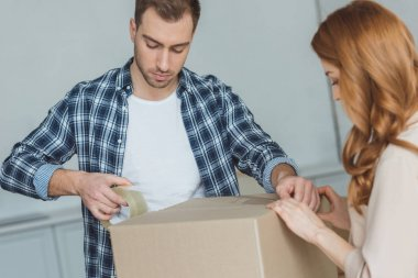 couple packing cardboard box with sticky tape together, relocation concept