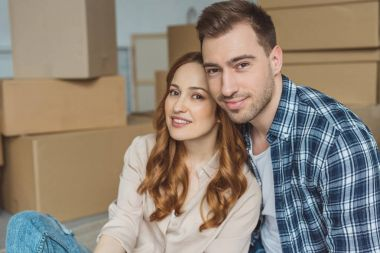 portrait of young couple at new apartment with cardboard boxes, relocation concept