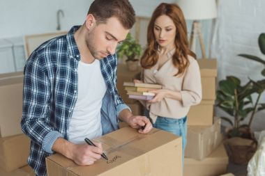 man signing cardboard box with wife with books in hands near by, moving home concept