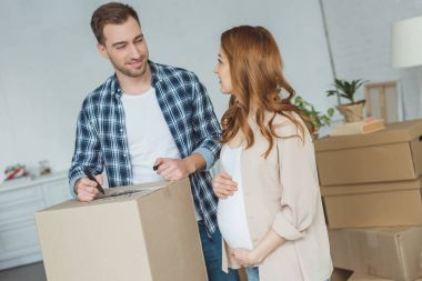 pregnant woman and husband at new apartment, relocation concept