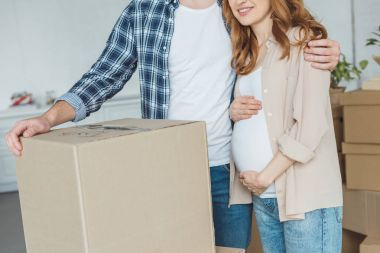 cropped shot of pregnant woman and husband at new apartment, relocation concept