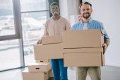 boldog többnemzetiségű férfiak gazdaság karton dobozok, és mosolyogva kamera áthelyezés során