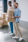 Fotografie young multiethnic men holding cardboard boxes and smiling at camera during relocation