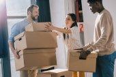 Fotografie usmívající se mnohonárodnostní spolupracovníky nesoucí lepenkové krabice během přemístění v nové kanceláři