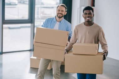 Happy multiethnic men holding cardboard boxes and smiling at camera during relocation stock vector