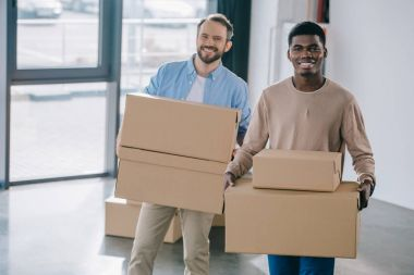 happy multiethnic men holding cardboard boxes and smiling at camera during relocation