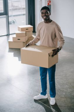 young african american man holding cardboard box and smiling at camera during relocation