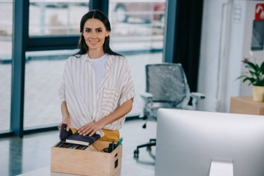 happy young businesswoman smiling at camera while unpacking office supplies at new workplace