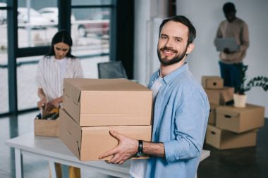 man holding cardboard boxes and smiling at camera while relocating with colleagues at new workplace